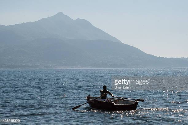 CONTENT] A man rows a rowboat towards the mountains in the distance on Chialolella Beach in Procida Italy