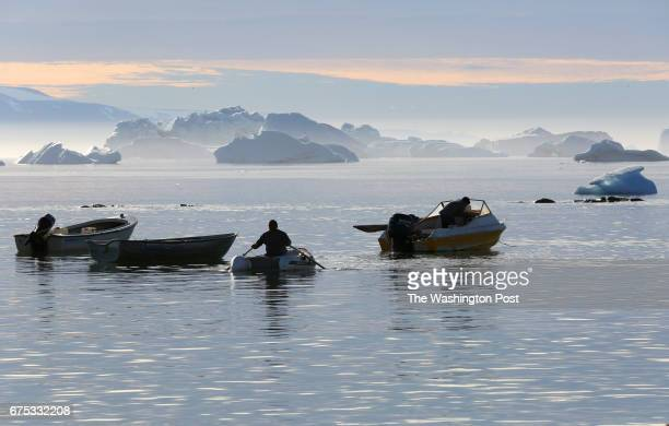 A man rows a small boat away from the tiny village of Qaanaaq Greenland where many people survive off of fishing and hunting on August 26 2016 by...