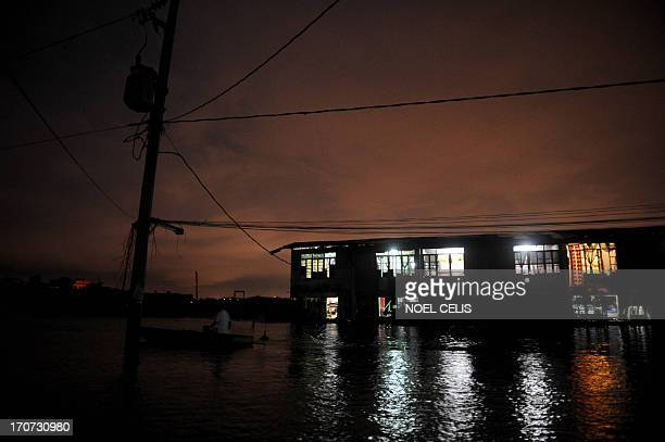 A man rows his boat as he passes on houses submerged in flood water at the Artex Compound in Malabon City Manila on June 5 2013 AFP PHOTO/NOEL CELIS