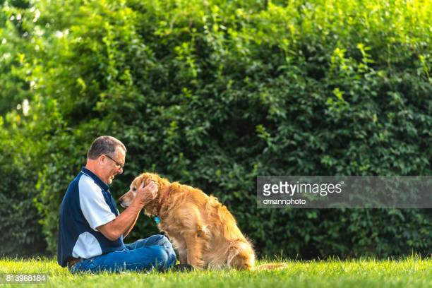 man rubbing his dog's ears at sunset - cmannphoto stock pictures, royalty-free photos & images