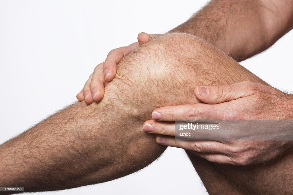 A man rubbing his knee because his knee is in pain : Stock Photo
