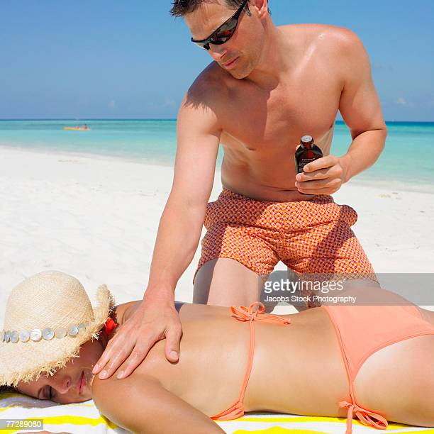 Man rubbing lotion on woman's back