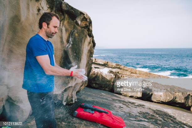 Man Rubbing Powder With Hands While Standing At Beach