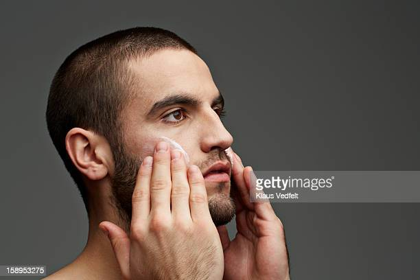 Man rubbing skin cream on the cheeks