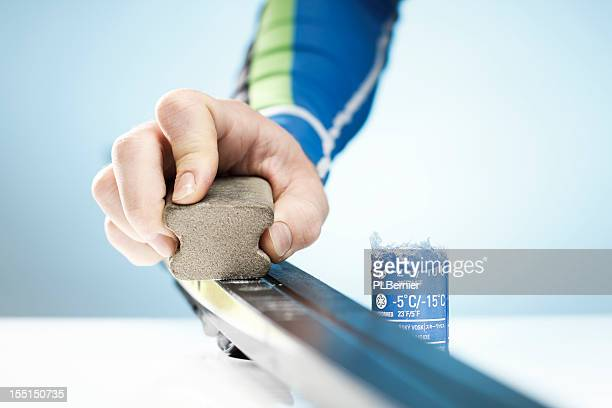 a man rubbing wax on his cross country skis - voorbereiding stockfoto's en -beelden