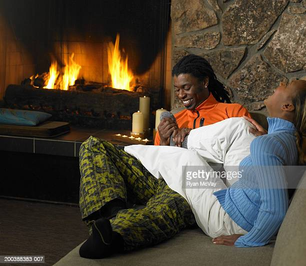 man rubbing woman's feet on sofa beside fireplace, laughing - tickling feet stock photos and pictures