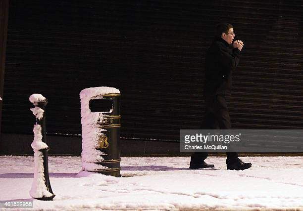 A man rubs his hands together as he walks through snow on his way to work on January 14 2015 in Antrim Northern Ireland The province experienced...