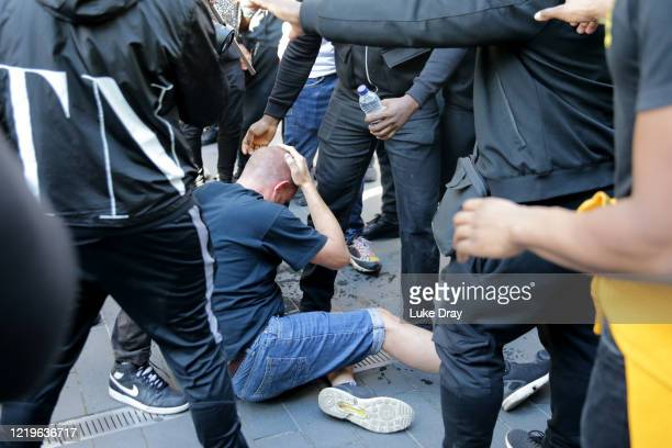 Man rubs his head as he sits on the ground after a group of men carried him away after he was allegedly attacked by some of the crowd of protesters...