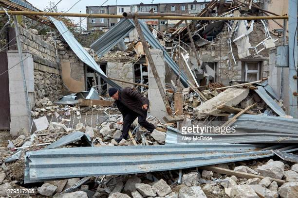 Man rummages through the remains of a home that was damaged by Azeri artillery on October 10, 2020 in Stepanakert, Nagorno-Karabakh. Residents of the...