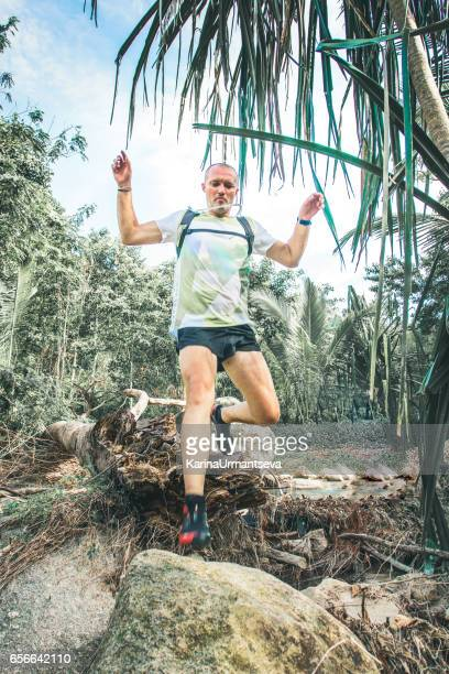 man run in the jungle - karina urmantseva stock pictures, royalty-free photos & images
