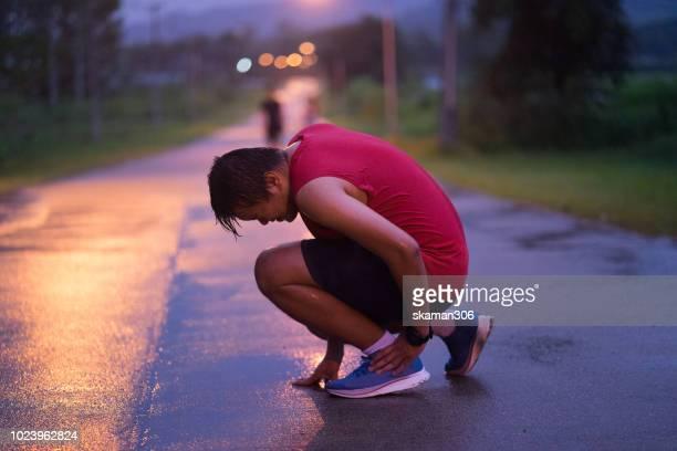 man runner injury after workout running in the rain - ligamento cruzado anterior fotografías e imágenes de stock