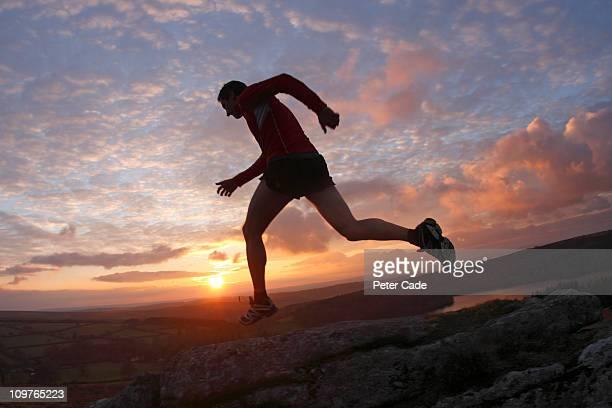 man running across moors at sunset
