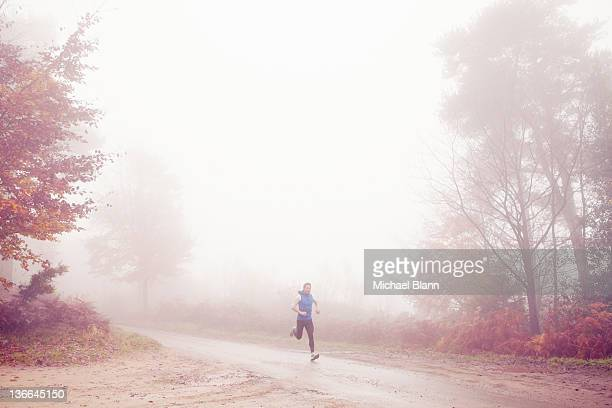 man running along countryside road in fog - newpremiumuk stock pictures, royalty-free photos & images