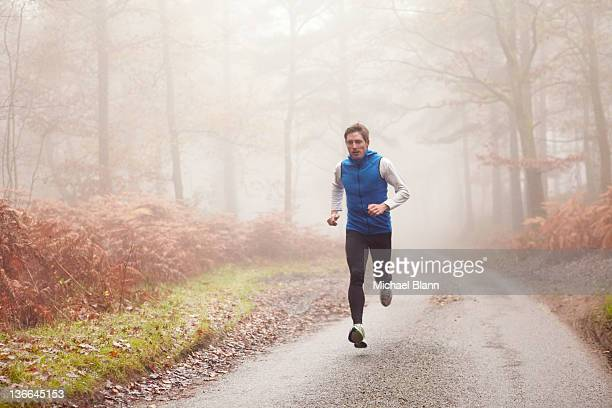 man running along countryside road in fog - jogging stock pictures, royalty-free photos & images