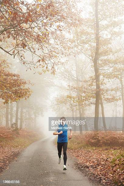 Man running along foggy countryside road