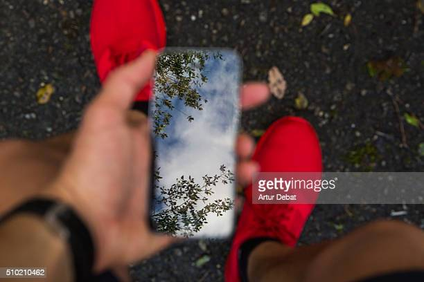 Man running and checking from personal point of view his smartphone with beautiful reflection and wearing a red trainers in the road asphalt.