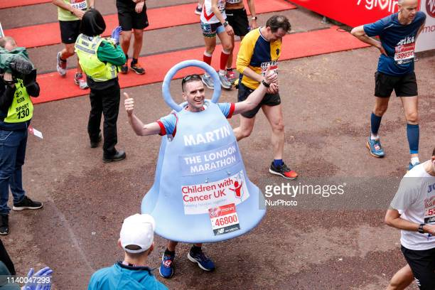 Man running as a bell crosses the finish line during the Virgin Money London Marathon in London England on April 28 2019 Nearly 43 thousand runners...