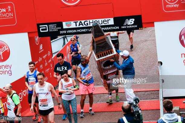 A man running as a Big Ben gets help to cross the finish line during the Virgin Money London Marathon in London England on April 28 2019 Nearly 43...