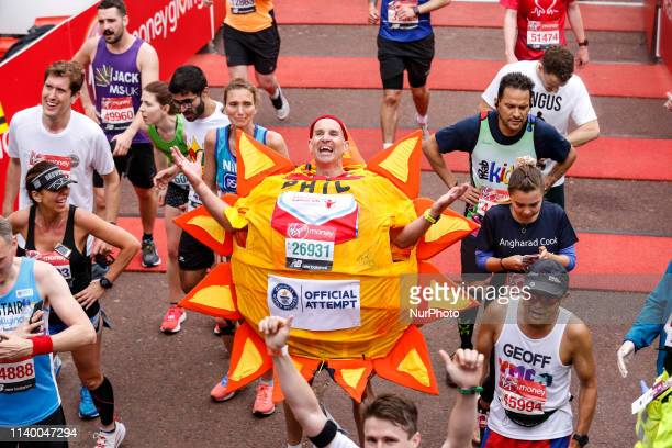 Man running as a sun crosses the finish line during the Virgin Money London Marathon in London England on April 28 2019 Nearly 43 thousand runners...