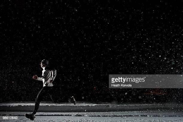 Man running at night in snowstorm.