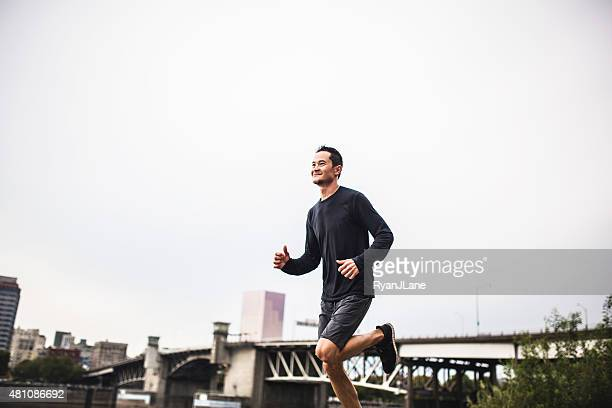 man running at portland waterfront - willamette river stock photos and pictures