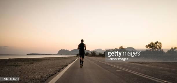man running at sea - hombre de espaldas playa fotografías e imágenes de stock