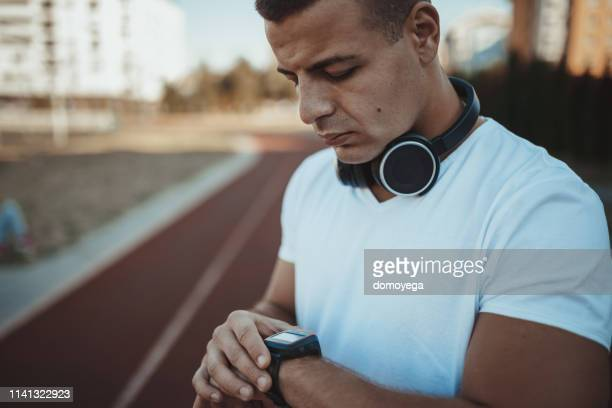 man running at the track and measuring time - men's track stock pictures, royalty-free photos & images