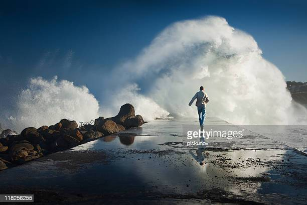 man running away to dangerous ocean waves - self harm stock photos and pictures