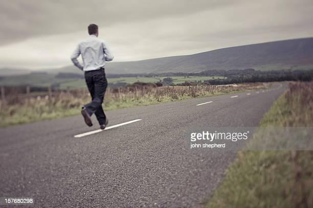 Hombre corriendo hacia abajo un vacío country road.