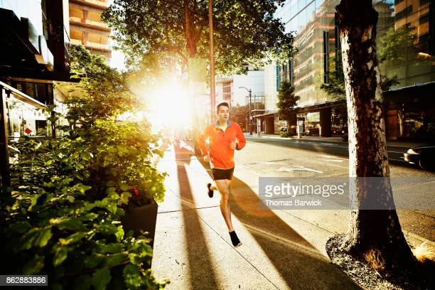 Man running down city sidewalk during early morning workout