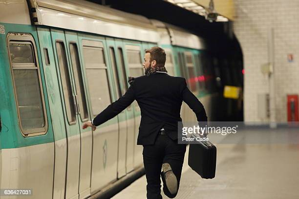 man running for underground train - dringendheid stockfoto's en -beelden