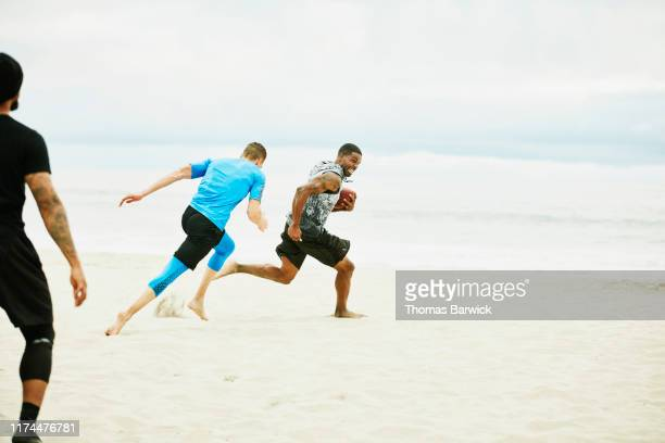 man running from defender during football game on beach with friends - rush american football stock pictures, royalty-free photos & images