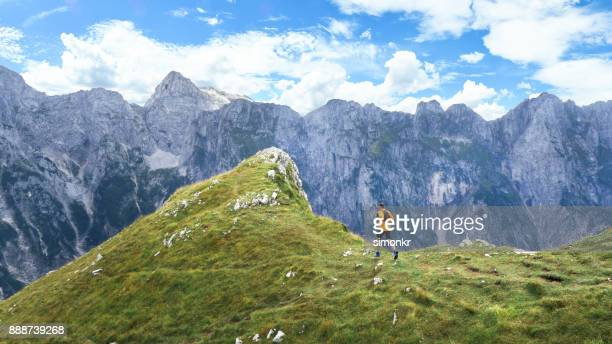 man running high in mountain grassy slope - cross country running stock pictures, royalty-free photos & images