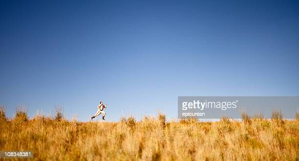 man running in big rubber boots and a superhero cape - runaway stock pictures, royalty-free photos & images
