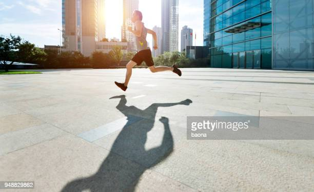 man running in city street - center athlete stock pictures, royalty-free photos & images