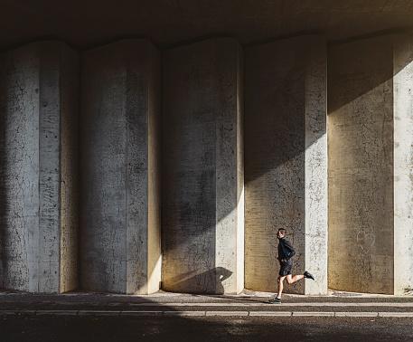 Man running in concrete underpass - gettyimageskorea