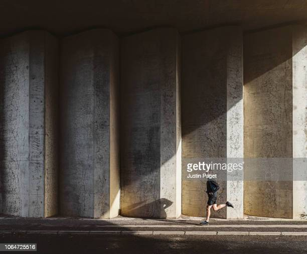 man running in concrete underpass - athleticism stock pictures, royalty-free photos & images