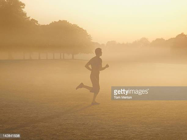 Man running in foggy field