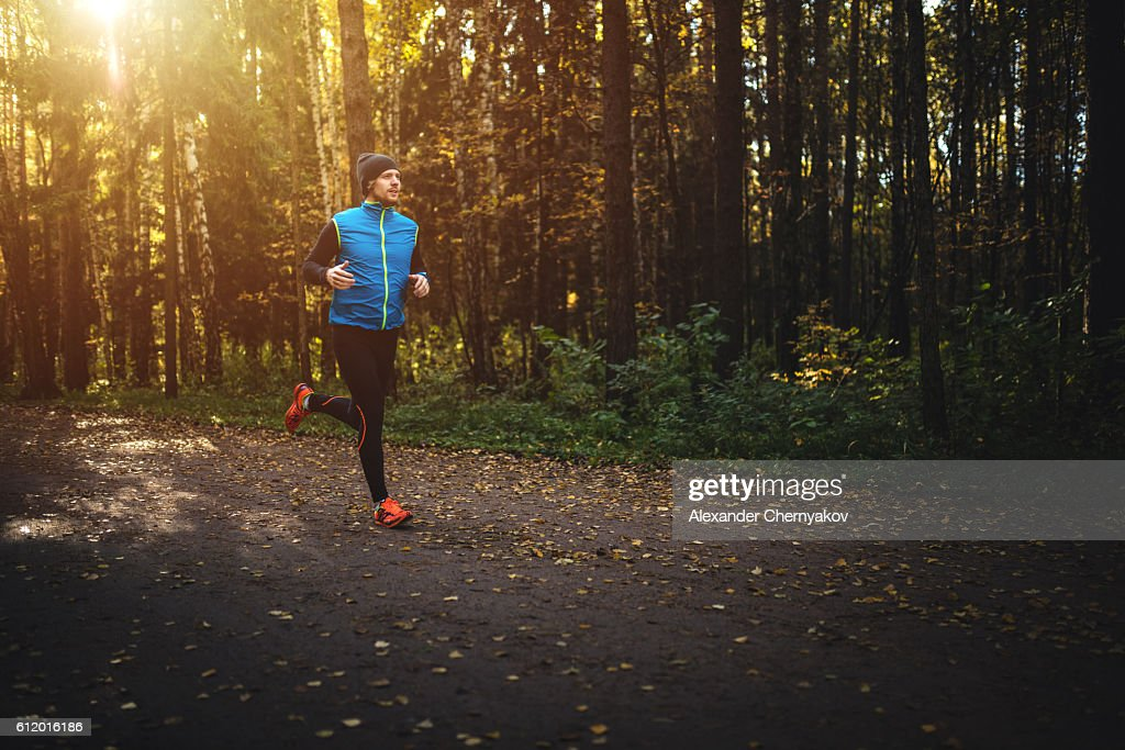 Man running in forest on sunrise : Stock Photo