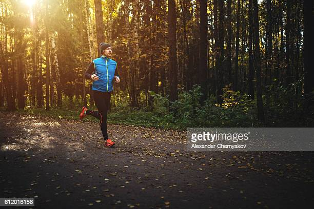 man running in forest on sunrise - running stock pictures, royalty-free photos & images