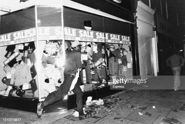 A man running in front of a clothing shop window damaged during the National Front meeting at Boulton Road Ladywood Birmingham UK 16th August 1977