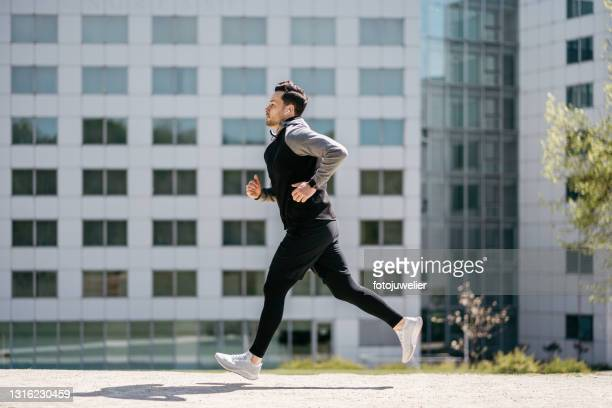 man running in front of modern buildings wearing wireless in-ear headphones - trousers stock pictures, royalty-free photos & images
