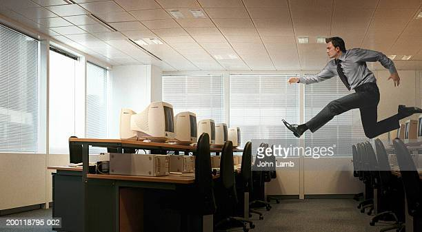 Man running in mid-air in office (Digital Composite)