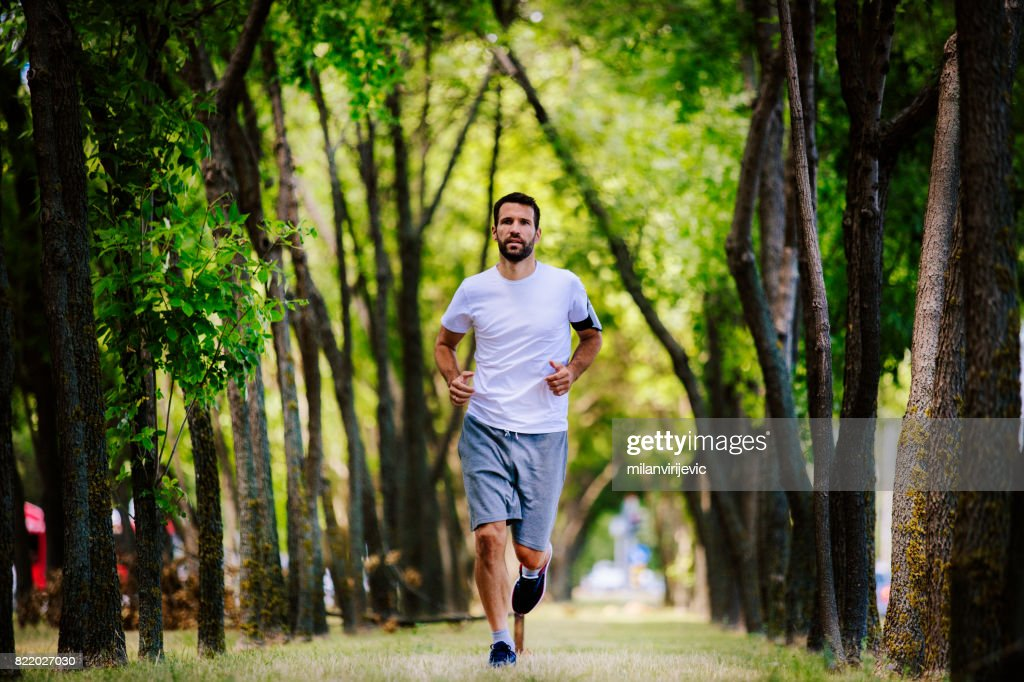 Man running in nature in early morning : Stock Photo