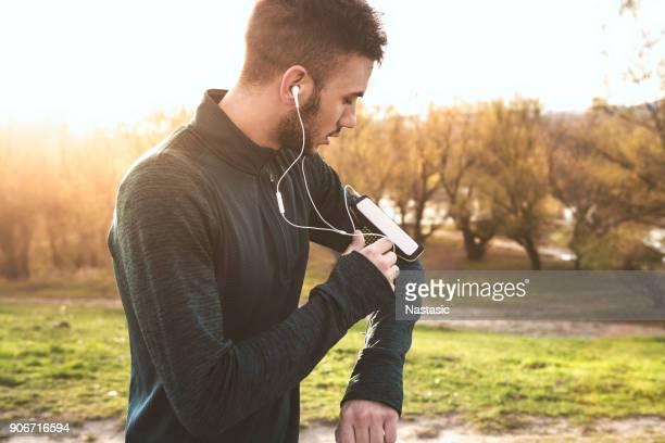 Man running in park, changing playlist