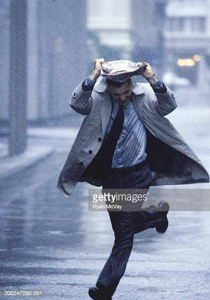 man running in rain in street, covering head with newspapers - トレンチコート ストックフォトと画像