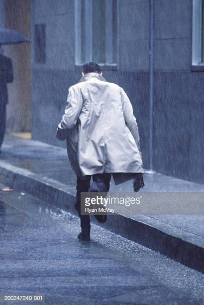 man running in rain, rear view - trench coat stock pictures, royalty-free photos & images
