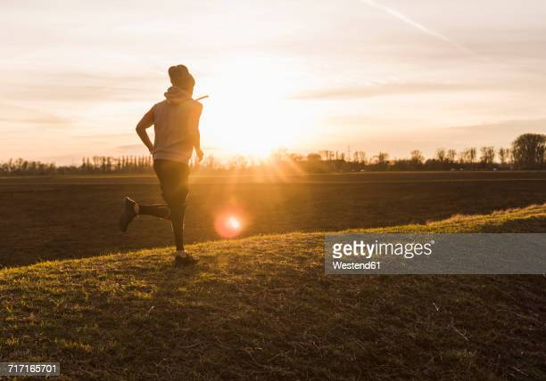 Man running in rural landscape at sunset