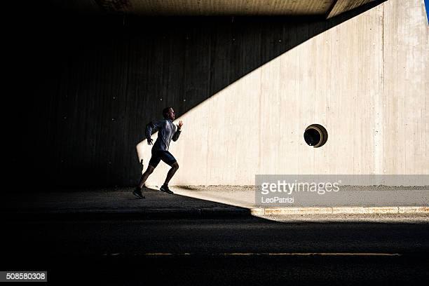 Mann läuft in der Stadt in am frühen Morgen