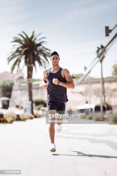 man running in the city streets during the day - quebra ventos imagens e fotografias de stock